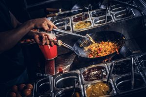 Cook is stirring vegetables in a wok. Cooking process in an Asian restaurant.