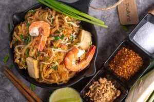 Top Table View of Thai Fried Noodles and Seasoning with Lemon There is a brown paper to tag the word THAILAND. and Famous Street Food of Thailand.
