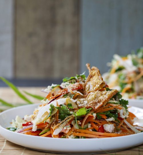 Thai salad with fresh vegetables, poached chicken and crispy chicken skin
